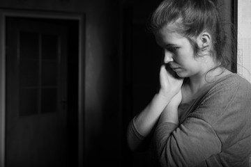 Lonely woman thinking about something. Photo taken in her room.