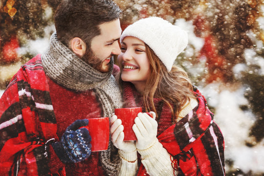 Young beautiful happy smiling couple holding red cups, mugs of hot drink. Models looking at each other, bundled up tartan blanket. Winter holidays, Christmas celebration, winter holidays concept