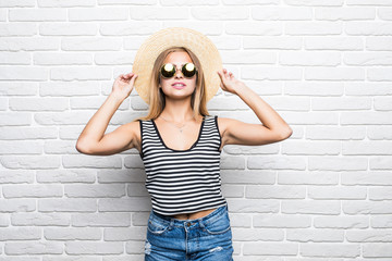 Young happy woman smiling in sunglasses and summer hat over white brick wall