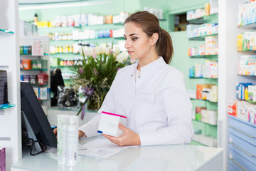 Portrait of woman pharmacist who is standing on her work place near cashbox in apothecary.