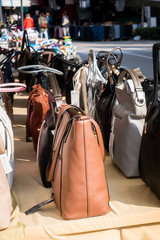 Women's handbags exposed for sale on a stall in the outdoor market.