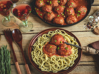 Homemade meatballs in tomato sauce with pasta on a plate. Frying pan on a wooden surface