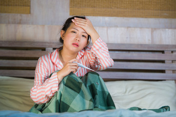 young beautiful and sweet Asian Korean girl in pajamas feeling sick at home bedroom suffering cold and flu taking temperature with thermometer in bed