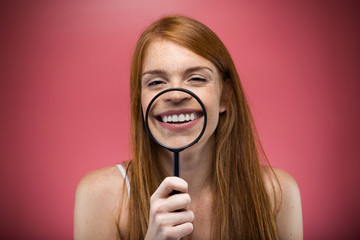 Pretty young woman showing teeth trought magnifying glass over pink background.