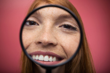 Pretty young woman showing face trought magnifying glass over pink background.