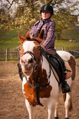 Young girl jockey riding a horse. / Young girl riding a horse
