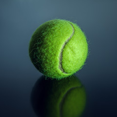 Tennis ball on a glossy background
