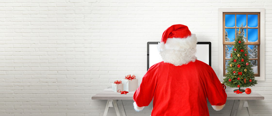 Santa work on a computer in his room. White brick wall in background with a free text space.