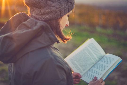 girl reading book at park in autumn sunset light