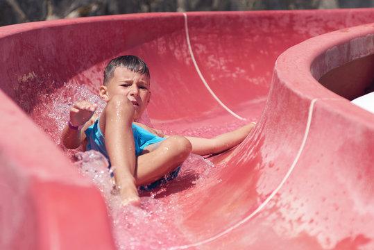 Cute European boy is sliding down red waterpark slide. He is enjoying his summer vacations.