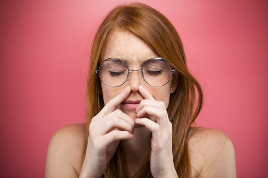 Redhead young woman pinching her nose over pink background.