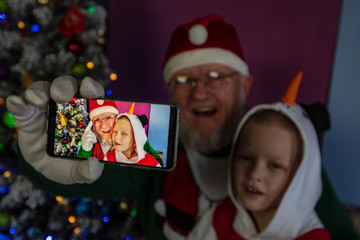 Elderly man with gray beard and glasses in Santa Claus hat with child shows selfie made by him on newest smartphone model against background of Christmas tree. Christmas Eve. Selective focus