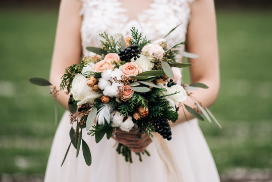 Winter bride's bouquet with roses, cotton, spruce, feathers, dried flowers in the hands of the bride