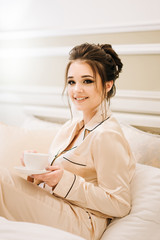 Beautiful young girl in Golden pajamas in a luxurious room with stylish hair and makeup lying in bed with a Cup of coffee. Morning bride.