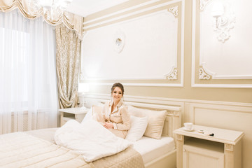Beautiful young girl in Golden pajamas in a luxurious room with stylish hair and makeup lying on the bed with a bandage for sleep . Bride's morning