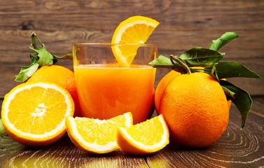 glass of fresh orange juice and oranges on wooden background