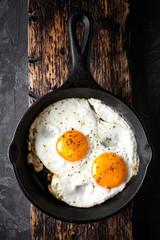Foto op Canvas Gebakken Eieren fried eggs in black skillet top view with space for a text