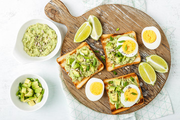 avocado toasts, healthy snack of grilled bread with guacamole slices avocado, boiled eggs, chia seeds and green onions