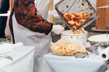 Fresh apple fritters being transferred into a bowl to be sprinkled with cinnamon sugar. Favourite snack on Christmas market in Switzerland. Swiss street food.