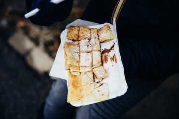 Close-up of freshly prepared crepes which are thin pancakes with chocolate spread filling outside at Christmas market. Popular warm street food in Switzerland especially in winter time. Swiss food tra