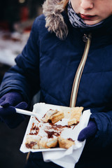 Young girl enjoying freshly prepared crepes which are thin pancakes with chocolate spread filling outside at Christmas market. Popular warm street food in Switzerland especially in winter time. Swiss