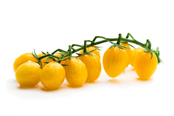 Bunch of fresh yellow cherry tomatoes with water drops isolated on white