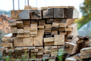 Stack of natural brown uneven rough wooden boards different size, cross-sectional view. Industrial timber for carpentry, building, repairing and furniture, lumber material for construction.