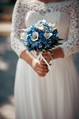 the bride is holding her bouquet on the background of a wedding dress