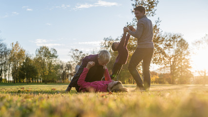 Young family of four playing in autumn park