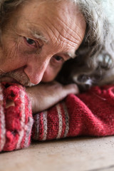 Senior man in torn sweater with worry in his eyes
