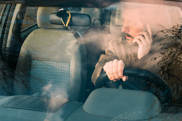 Front view of man driving car and talking on mobile
