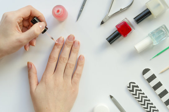 Woman at home makes a manicure, prepare for applying nail polish, causes protection skin defender on hands. Frame manicure equipment on white background. Flat lay mock up. Manicurist concept top view