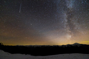 Majestic view of fantastic starry dark sky on winter night. Milky Way and falling star over magnificent mountain ridge snow-capped peaks. Breathtaking panorama of beauty and magic of nature.