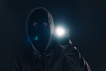 Burglar intruder with flashlight torch at night