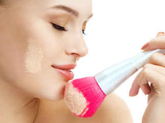 Close up of woman applies dry powder on her face using makeup brush on white background. Beauty concept