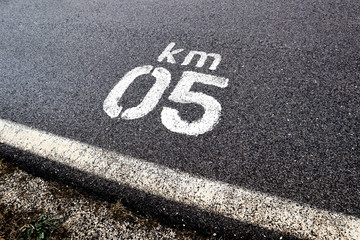 close up of letters and number km 05 on asphalt road, wet asphalt road texture