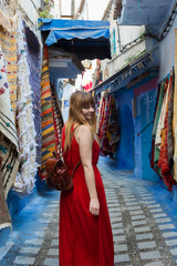Smiling model walking in the blue medina of Chefchaouen. Colorful african carpets on walls.