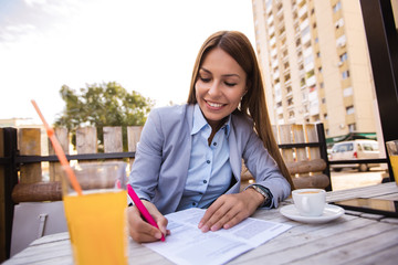 Portrait of young businesswoman holding pen at outdoor cafe
