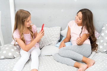 Online stream vlog channel. Sisters in pajamas relax bedroom and take funny photo for social network account. Leisure and fun. Social networks concept. Girls friends taking photo for social networks