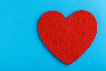 Red felt heart on bright blue background. St. Valentine's day
