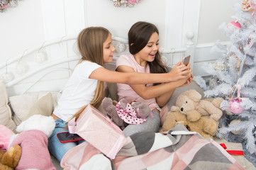Capturing the moment. Small girls use smartphone in bed. Texting Christmas and New Year greetings by phone. Merry Christmas and Happy New Year. Happy small children with mobile phone