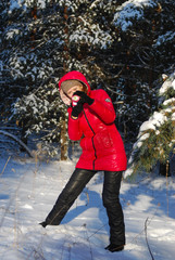 Woman in winter, female photographer takes picture on digital camera outdoors in cold day on blurred forest background, empty copy space, view profile
