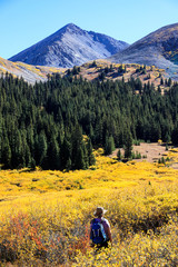 Woman hiking during autumn at Mayflower Gulch, Colorado