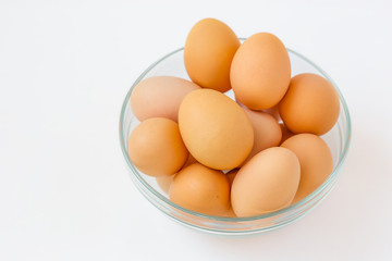 Many brown eggs in a glass bowl.