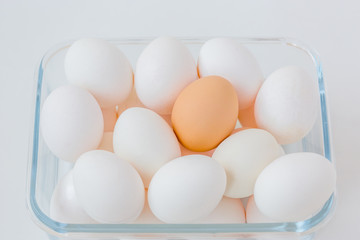 Many white eggs with one brown egg in a glass bowl.