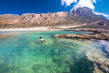 Poster Turkoois Young attractive man swimming in Balos lagoon on Crete island with azure clear water, Greece, Europe