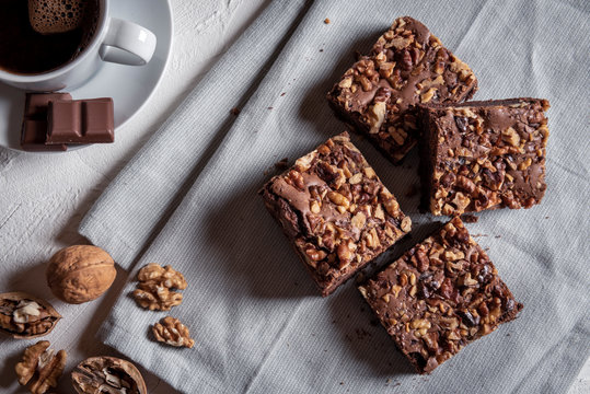 Brownie cakes with walnuts on a kitchen towel. Directly above view