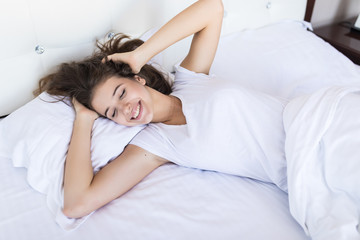 Portrait of young smiling pretty lady lies in bed indoors.