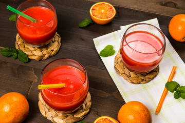 red drinks with oranges and mint on the wooden table