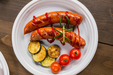 Plate with grilled sausage, cucumber and tomatoes on the wooden table